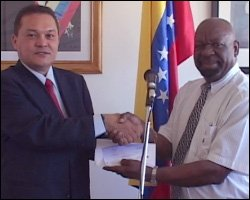 Cruz de Jesus Bello presents cheque to Gus Williams