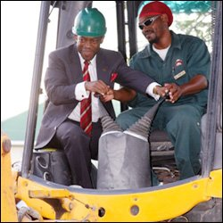 PM Douglas Tries His Hand On A Backhoe