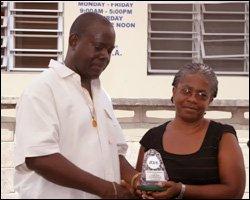 Valerie James Receives Plaque From Robelto Hector